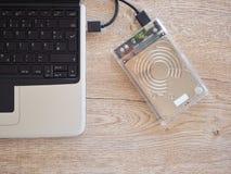 De aandrijving wordt verbonden met een notitieboekjecomputer op een houten bureau Met het concept het houden van informatie in de stock foto's
