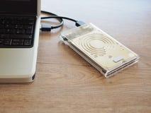 De aandrijving wordt verbonden met een notitieboekjecomputer op een houten bureau Met het concept het houden van informatie in de stock afbeelding