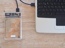 De aandrijving wordt verbonden met een notitieboekjecomputer op een houten bureau Met het concept het houden van informatie in de royalty-vrije stock afbeeldingen
