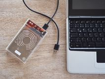 De aandrijving wordt verbonden met een notitieboekjecomputer op een houten bureau Met het concept het houden van informatie in de stock afbeeldingen