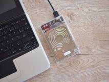 De aandrijving wordt verbonden met een notitieboekjecomputer op een houten bureau Met het concept het houden van informatie in de royalty-vrije stock foto