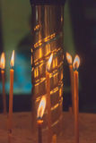 De aangestoken kaarsen in kerk tegen Stock Afbeeldingen