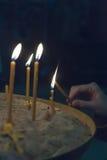 De aangestoken kaarsen in kerk tegen Stock Fotografie