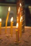 De aangestoken kaarsen in kerk tegen Royalty-vrije Stock Fotografie