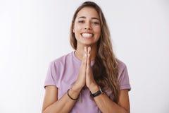 De aanhankelijke vrouwelijke vriend die gunst vragen die ruim het houden van handen glimlachen bidt het grijnzen bedelend de drin royalty-vrije stock afbeeldingen