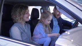 De aankoop van de familieauto, glimlachend paar met weinig dochter inspecteert familie automobiele golvende zeer belangrijke en g stock footage