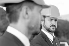 De aannemers controleren bouwwerkzaamheden Het concept van de bouw De managers dragen slimme kostuums, banden en bouwvakkers op a royalty-vrije stock afbeelding