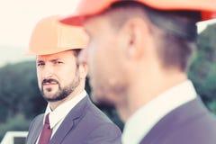 De aannemers controleren bouwwerkzaamheden Het concept van de bouw De managers dragen slimme kostuums, banden en bouwvakkers op a royalty-vrije stock fotografie