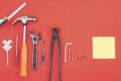 De aannemershulpmiddelen van de moersleutelingenieur op een denimarbeiders, de rode achtergrond van A met de hulpmiddelen van de  royalty-vrije stock foto