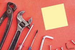 De aannemershulpmiddelen van de moersleutelingenieur op een denimarbeiders, de rode achtergrond van A met de hulpmiddelen van de  stock afbeeldingen