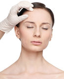 De aanraking van de schoonheidsspecialist en de vrouwengezicht van de examengezondheid. Stock Afbeeldingen