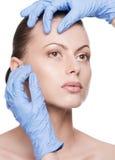 De aanraking van de schoonheidsspecialist en de vrouwengezicht van de examengezondheid royalty-vrije stock foto's