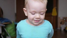 De aantrekkelijke 2 éénjarigenjongen bekijkt de camera en de glimlachen en verandert gelaatsuitdrukkingen Huismeubilair Blauwe t- stock videobeelden