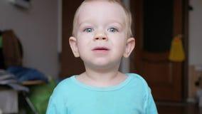 De aantrekkelijke 2 éénjarigenjongen bekijkt de camera en de glimlachen en verandert gelaatsuitdrukkingen Huismeubilair Blauwe t- stock footage