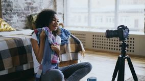 De aantrekkelijke Afrikaanse videoblog van de meisjesopname over haar garderobe voor reis met dslrcamera thuis Stock Foto
