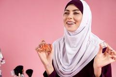 De aantrekkelijke Arabische vrouw in hijab gebruikt parfum stock afbeelding