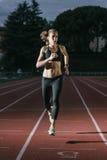 De aantrekkelijke Atleet Running On Track van het vrouwenspoor Royalty-vrije Stock Fotografie