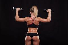 De aantrekkelijke atletische vrouw pompt omhoog spieren met domoren, achterdiemening op donkere achtergrond met copyspace wordt g Stock Afbeelding