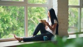 De aantrekkelijke Aziatische studente leest boek en glimlacht zitting op vensterrichel in moderne flat Hobby, de jeugd stock videobeelden