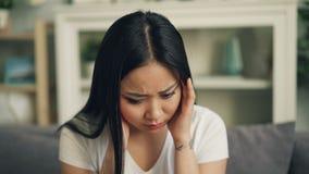 De aantrekkelijke Aziatische vrouw lijdt aan sterke hoofdpijn wat betreft haar hoofd het masseren tempels thuis binnen zittend stock footage