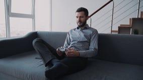 De aantrekkelijke baardmens zit op bus en speelt bij videospelletje thuis houdend digitaal technologiecontrolemechanisme stock videobeelden