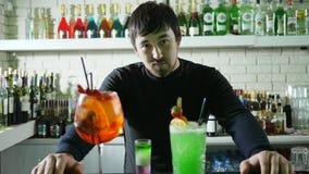 De aantrekkelijke barman bevindt zich achter bar met gekleurd cocktails verfraaid fruit en ijs, partij van flessen met duur stock videobeelden