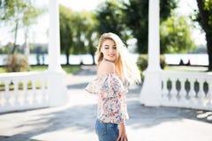 De aantrekkelijke blonde jonge vrouw loopt in de stad Draai rond Royalty-vrije Stock Foto's