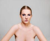De aantrekkelijke blonde naakte vrouw met donker oog maakt omhoog