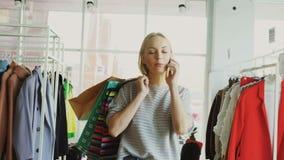 De aantrekkelijke blonde vrouw loopt tussen planken en sporen in grote opslag en spreekt op mobiele telefoon Zij draagt stock videobeelden