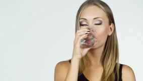 De aantrekkelijke blondevrouw drinkt water op een witte achtergrond stock videobeelden