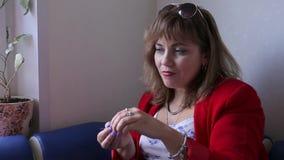 De aantrekkelijke bruin-haired vrouw in rode kleren zit in de ruimte kijkt uit het venster en eet druiven Gezond voedselconcept stock video
