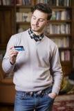 De aantrekkelijke creditcard van de jonge mensenholding, die het bekijken Stock Fotografie