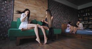 De aantrekkelijke dames in de ochtend hebben een grote stemming in pyjama's die op de bank zitten en met elkaar op babbelen stock video