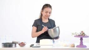 De aantrekkelijke donkerbruine chef-kok van het meisjesgebakje in schort ranselt roomcake in een metaalkom stock footage