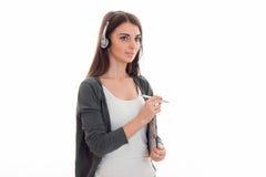 De aantrekkelijke donkerbruine die vrouw van de vraagbeambte met hoofdtelefoons en microfoon op witte achtergrond wordt geïsoleer Royalty-vrije Stock Foto's