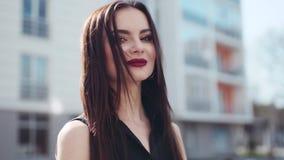 De aantrekkelijke donkerbruine vrouw met hartstochtelijke rode lippen, en neus het doordringen kijken aan de camera en gaan de zo stock videobeelden