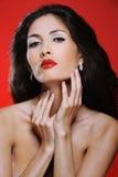De aantrekkelijke donkerbruine vrouw met prachtig haar raakt haar hals Royalty-vrije Stock Fotografie