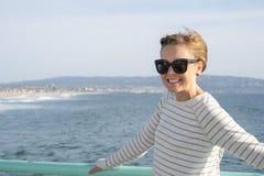 De aantrekkelijke donkerbruine vrouw stelt op de het Strandpijler van Manhattan in Californië op de oceaan Het dragen van toevall royalty-vrije stock afbeeldingen