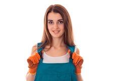 De aantrekkelijke donkerbruine vrouwenbouwer maakt vernieuwing en het glimlachen op camera in eenvormig geïsoleerd op witte achte Royalty-vrije Stock Foto's