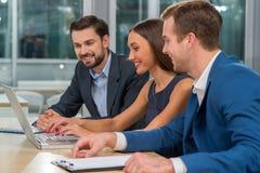 De aantrekkelijke drie partners spreken in bureau Stock Afbeeldingen