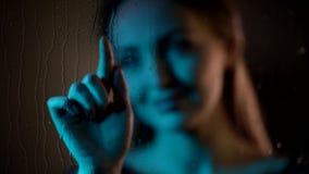 De aantrekkelijke dromerige jonge Kaukasische vrouw bekijkt glasvenster trekt een hart met vingertoppen in het nacht blauwe neonl stock video