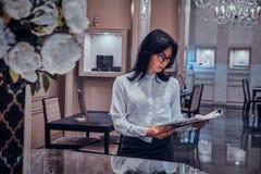 De aantrekkelijke elegante vrouw let op tijdschrift bij elegante juwelenboutique stock fotografie