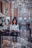 De aantrekkelijke elegante vrouw let op tijdschrift bij elegante juwelenboutique royalty-vrije stock foto