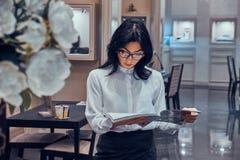 De aantrekkelijke elegante vrouw let op tijdschrift bij elegante juwelenboutique royalty-vrije stock afbeeldingen