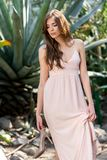 de aantrekkelijke elegante vrouw in roze kledingsholding hielt terwijl het stellen stock foto