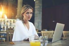 De aantrekkelijke elegante vrouwen die bij de lijst met open laptop computer tijdens ochtend zitten ontbijten Royalty-vrije Stock Afbeeldingen