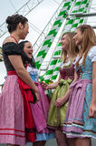 De aantrekkelijke en blije vrouw in Duitse Oktoberfest met traditionele dirndl kleedt zich, groot wiel op de achtergrond Stock Afbeeldingen