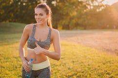 De aantrekkelijke fitness vrouw in sport kleedt omhoog gesturing duimen Royalty-vrije Stock Fotografie