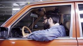 De aantrekkelijke gebaarde mens met lang haar zit in rode auto en kijkt uit venster stock video