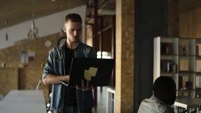 De aantrekkelijke geconcentreerde jonge bedrijfsmens loopt met laptop in zijn hand en het typen Kaukasische mens die binnen werke stock videobeelden